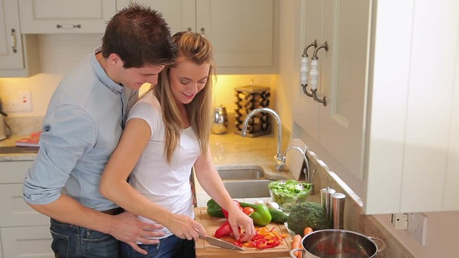 husband helping wife in kitchen