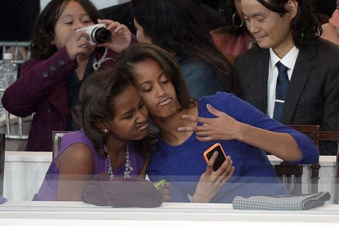 Sasha and Malia taking selfie
